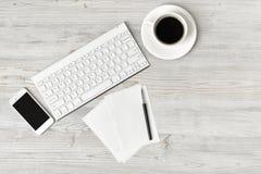 Рабочее место с чашкой кофе, клавиатурой, smarthphone, белыми листами и ручкой на деревянной поверхности в взгляд сверху стоковые фото
