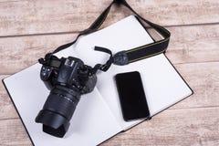 Рабочее место фотографов с книгой, телефоном и камерой на деревянных животиках Стоковое Изображение RF