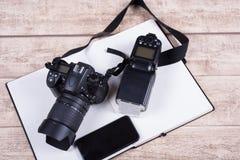 Рабочее место фотографов с книгой, телефоном и камерой на деревянных животиках Стоковые Фото
