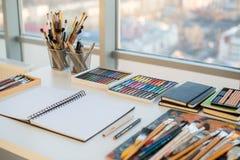 Рабочее место художника в взгляде со стороны заказа Дизайнерский стол с оборудованием чертежа Домашняя студия для художника стоковые фото