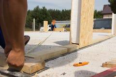 Рабочие классы принимая измерение на строительной площадке Стоковая Фотография