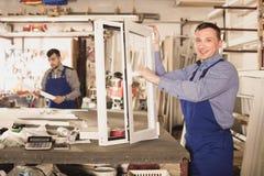 Рабочие классы проверяя продукцию обрабатывающей промышленности PVC в мастерской Стоковое Фото