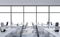 Рабочие места в современном панорамном офисе, космосе экземпляра в окнах открытое пространство Белые таблицы и черные кожаные сту Стоковые Изображения