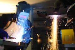 Рабочие сталелитейной промышленности сваривая и режа стоковое изображение