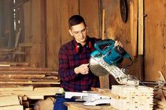 Рабочий класс одел в checkered рубашке проверяя круглую пилу на лесопилке Тимберсы на предпосылке Стоковое Изображение
