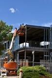 Рабочий-строители высокие на гидравлическом подъеме на строительной площадке стоковые фото