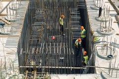 Рабочий-строители устанавливают арматуру для нового здания Стоковые Изображения