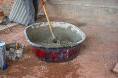 Рабочий-строитель вручную смешивая бетон в подносе смесителя стоковые фото