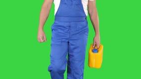 Рабочий-строитель в трудной шляпе держа пластиковую банку и идя на зеленый экран, ключ Chroma сток-видео