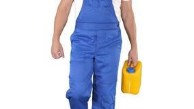 Рабочий-строитель в трудной шляпе держа пластиковую банку и идя на белую предпосылку сток-видео