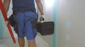 Рабочий-строитель идя через квартиру с резцовой коробкой сток-видео
