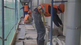 Рабочий-строитель использует автомат для резки силы во время работы на лесах видеоматериал