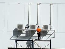 Рабочий-строитель используя поднимаясь заграждение стоковая фотография