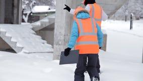 Рабочий-строитель и инженер говоря на строительной площадке Работники в шлемах вне здания акции видеоматериалы