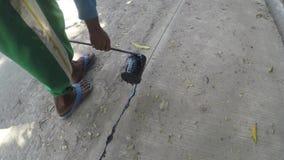 Рабочий-строитель лить горячий расплавленный асфальт между блоками транспортной развязки акции видеоматериалы
