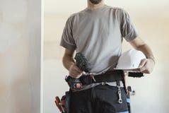 Рабочий-строитель представляя с шлемом и сверлом безопасности стоковые фото