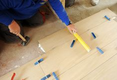 Рабочий-строитель проверяя с ровным инструментом правильное размещение новой мостоваой штейнгута фарфора кроет черепицей стоковое фото