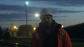 Рабочий-строитель стоя утомлянный в сумерк опрокинутый 4K сток-видео
