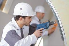 Рабочий-строитель с инструментами и сверлом восстанавливая дом стоковое изображение rf