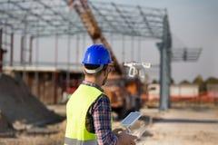Рабочий-строитель с трутнем на строительной площадке стоковое изображение