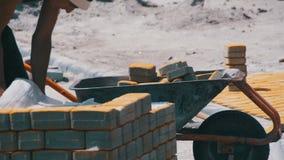 Рабочий-строитель управляет тачкой с вымощая камнями на строительной площадке сток-видео