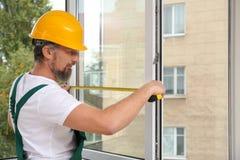 Рабочий-строитель устанавливая новое окно стоковое фото rf