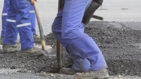 Рабочий-строители выравнивая свежую мостоваую асфальта видеоматериал