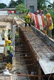 Рабочий-строители изготовляют бар и форма-опалубку подкрепления подпорной стенки на строительной площадке Стоковое Изображение RF