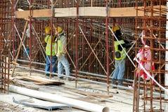 Рабочий-строители изготовляют стальное подкрепление для бетонной стены на строительной площадке Стоковая Фотография RF