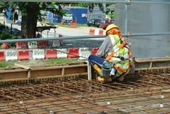 Рабочий-строители изготовляя бар подкрепления сляба пола Стоковые Фотографии RF