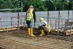 Рабочий-строители изготовляя бар подкрепления сляба пола Стоковые Изображения RF