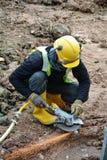 Рабочий-строители используя точильщика конструкции для того чтобы заточить сталь на строительной площадке Стоковая Фотография RF