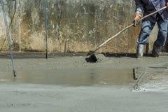 Рабочий-строители лить бетон стоковое изображение