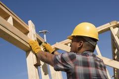 Рабочий-строитель бить молотком ноготь молотком на рамке тимберса Стоковое Изображение RF