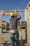 Рабочий-строитель бить молотком ноготь молотком на рамке тимберса Стоковое Фото