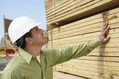 Рабочий-строитель в защитном шлеме проверяя пиломатериал стоковое фото