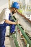 Рабочий-строитель в одежде работы держит шлем конструкции, мобильный телефон и номер шкалы в руке Работа на большой возвышенности стоковое изображение rf