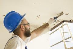 Рабочий-строитель в одежде работы, защитных перчатках и шлеме на месте Извлеките старый шпатель краски от потолка Стоковое фото RF