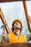 Рабочий-строитель держа молоток на месте Стоковые Фото
