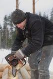 Рабочий-строитель делая продольные зазубрины на журнале используя c Стоковая Фотография RF