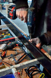 Рабочий-строитель используя сверло для того чтобы установить окно Стоковое фото RF