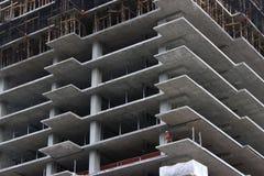 Рабочий-строитель на незаконченном многоэтажном здании стоковая фотография