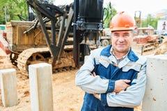 Рабочий-строитель перед машиной водителя кучи Стоковая Фотография