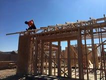 Рабочий-строитель работая на обрамляя процессе для новой дом стоковое изображение