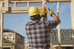 Рабочий-строитель работая на рамке тимберса Стоковые Изображения