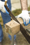 Рабочий-строитель режет ручную пилу на части сырцовой древесины стоковая фотография