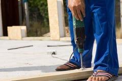 Рабочий-строитель сверля древесину на месте Стоковое Изображение
