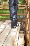 Рабочий-строитель стоя на штабелированное деревянном Стоковые Фото