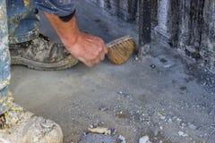 Рабочий-строитель с бетоном 2 веника подметая Стоковое фото RF