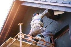 Рабочий-строитель термально изолируя дом с стеклянной ватой и фольгой стоковые фото
